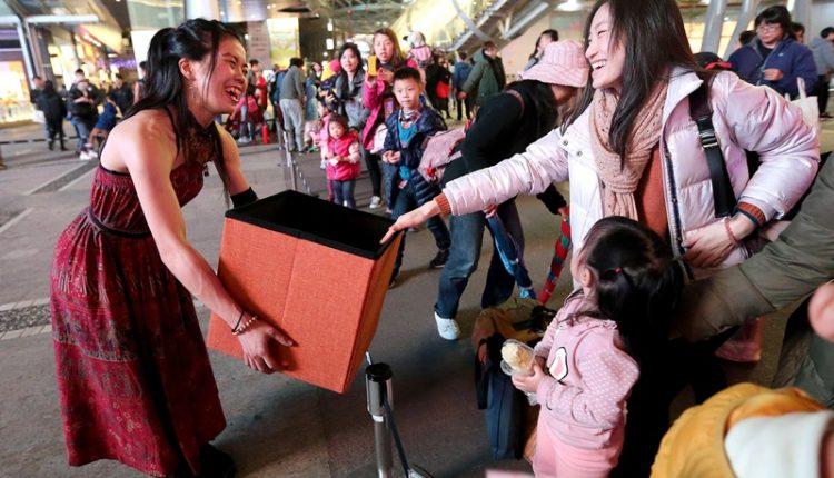 火舞演出後,團員們拿著打賞箱請觀眾樂捐,是他們一天收入的來源。(趙雙傑攝)
