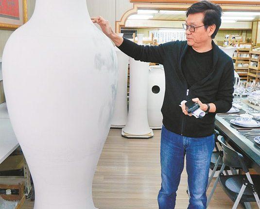 呂兆炘說明高逾2公尺的大花瓶的製作及彩繪技巧。(陳俊雄攝)