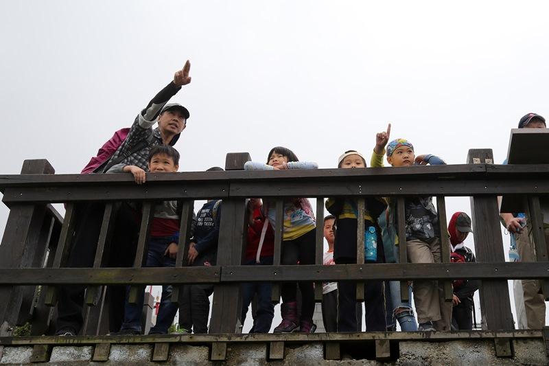崔德龍(左)說,孩子透過爬山時對自我身體的控制,進而學習控管問題情緒。(王爵暐攝)