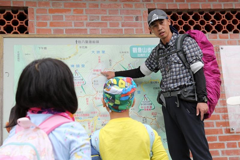 崔德龍老師(右)在爬山前,為小朋友講解登山路線。(王爵暐攝)