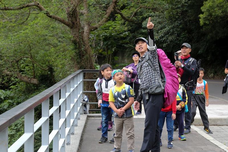 崔老師(右)與指著遠處的山稜線,對孩子解說攻頂的路線。(王爵暐攝)