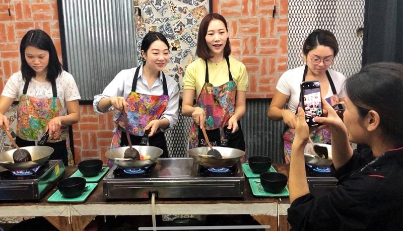 學員們在料理廚房內開心學廚藝,還有老師拍照留念。(姚志平攝)