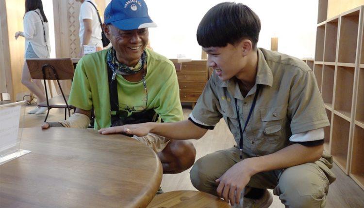 第二次參展的蘇駿(右),在木工畢業展中熟練的向遊客介紹他們的木工作品。(季志翔攝)