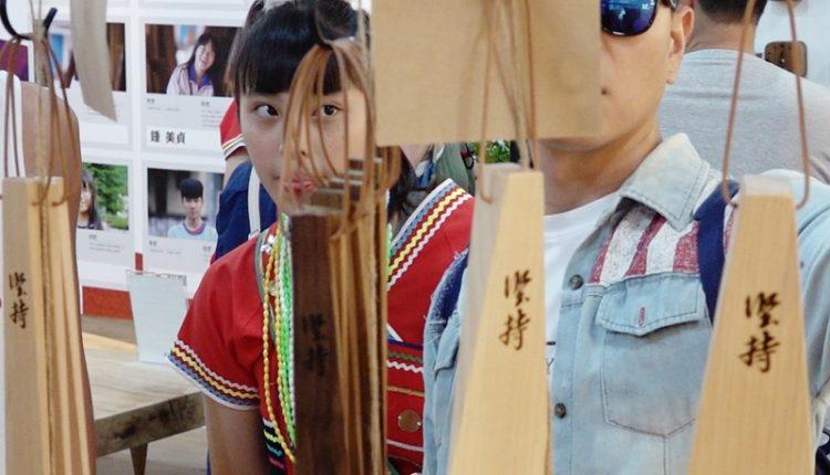 在展場中,木工班學生黃怡萱滿心期待的看著遊客把玩她的工藝作品。(季志翔攝)