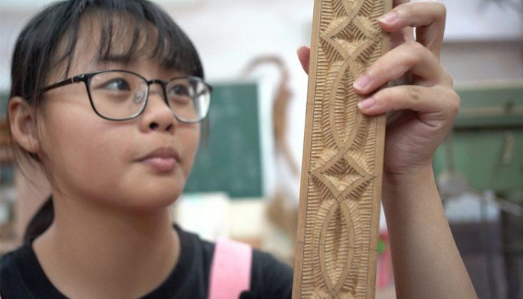 黃宇佟是以原住民為主的玉東國中學生中少數的漢族之一,她拿著刻有「魚」圖騰的木頭解釋著阿美族的傳統文化。(季志翔攝)