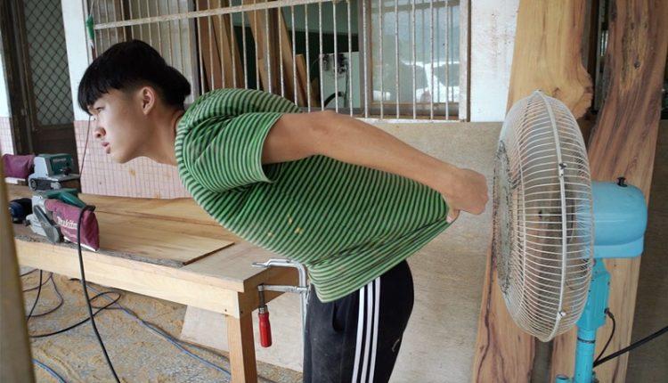 玉東國中木工班學生蘇駿用強力電扇吹走他身上的汗水與木屑。(季志翔攝)