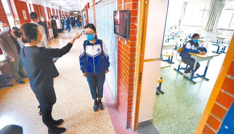4月18日,北京一中學模擬學生開學流程,學生在教室門口測量額溫。(中新社)